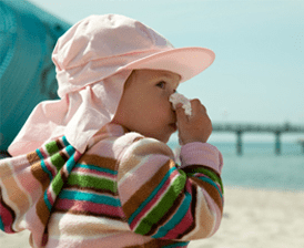 Sneezing child on beach